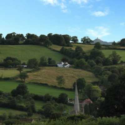 View across Croscombe to Hillview Cottage with Glastonbury Tor in the distance